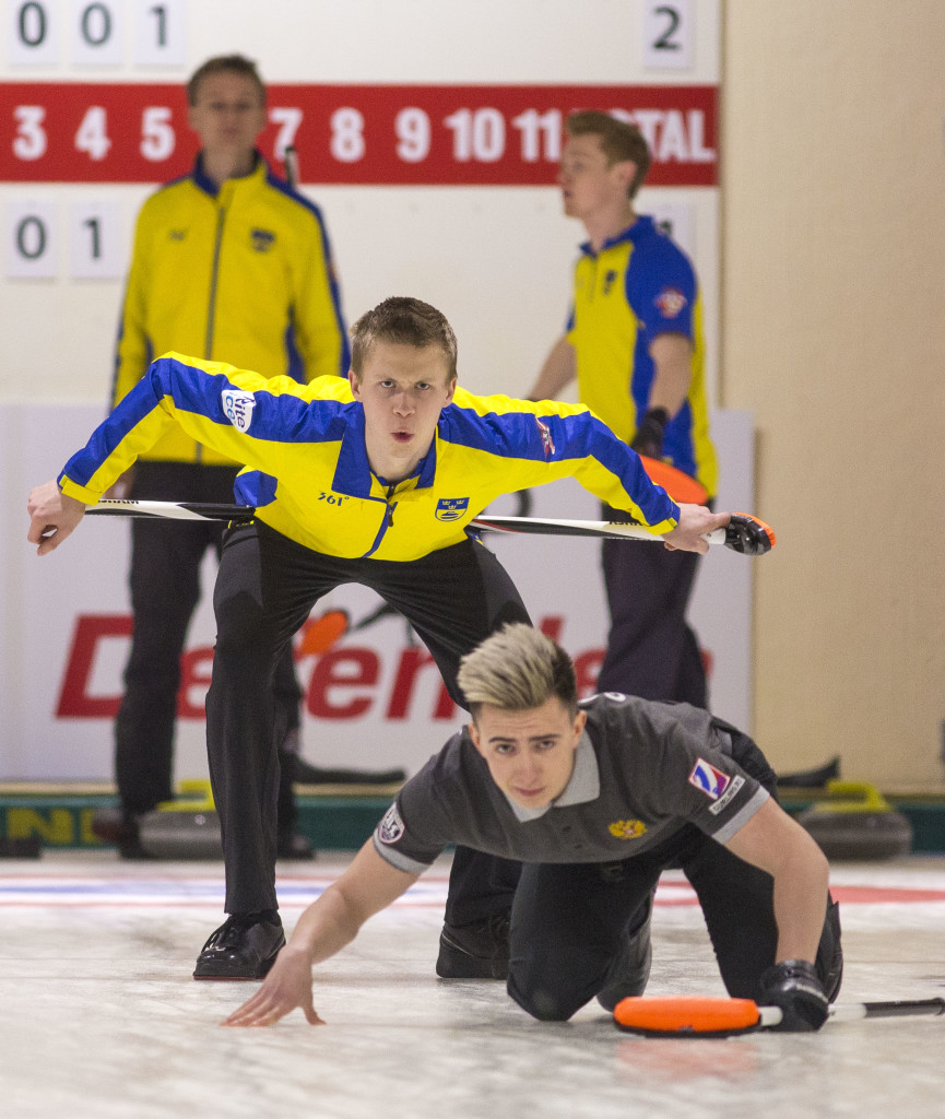 Axel Sjoeberg of Sweden watches over Daniil Goryachev of Russia's shoulder as Goryachev's shot makes its way down the sheet. The Russian men's team was relegated to the junior-b world championships next year. Photo by Marissa Tiel