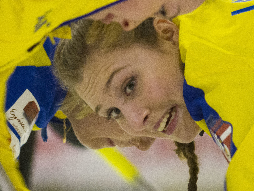Maria Larsson of Team Sweden sweeps a rock. down the ice at the VoIP Defender World Junior Curling Championships 2016. Photo by Marissa Tiel