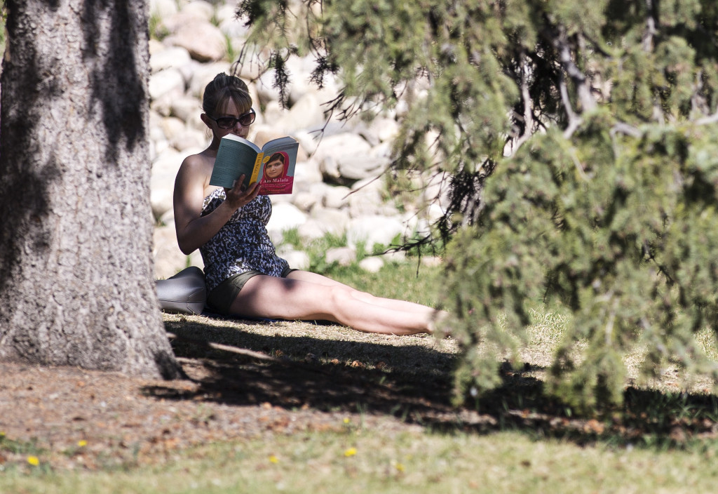 Alesia Fieldberg reads under a tree at Prince's Island Park in Calgary, Alta., on Monday, April 13, 2015. Calgary is on track to break a 100-year-old high temperature record today. Marissa Tiel/Postmedia Network
