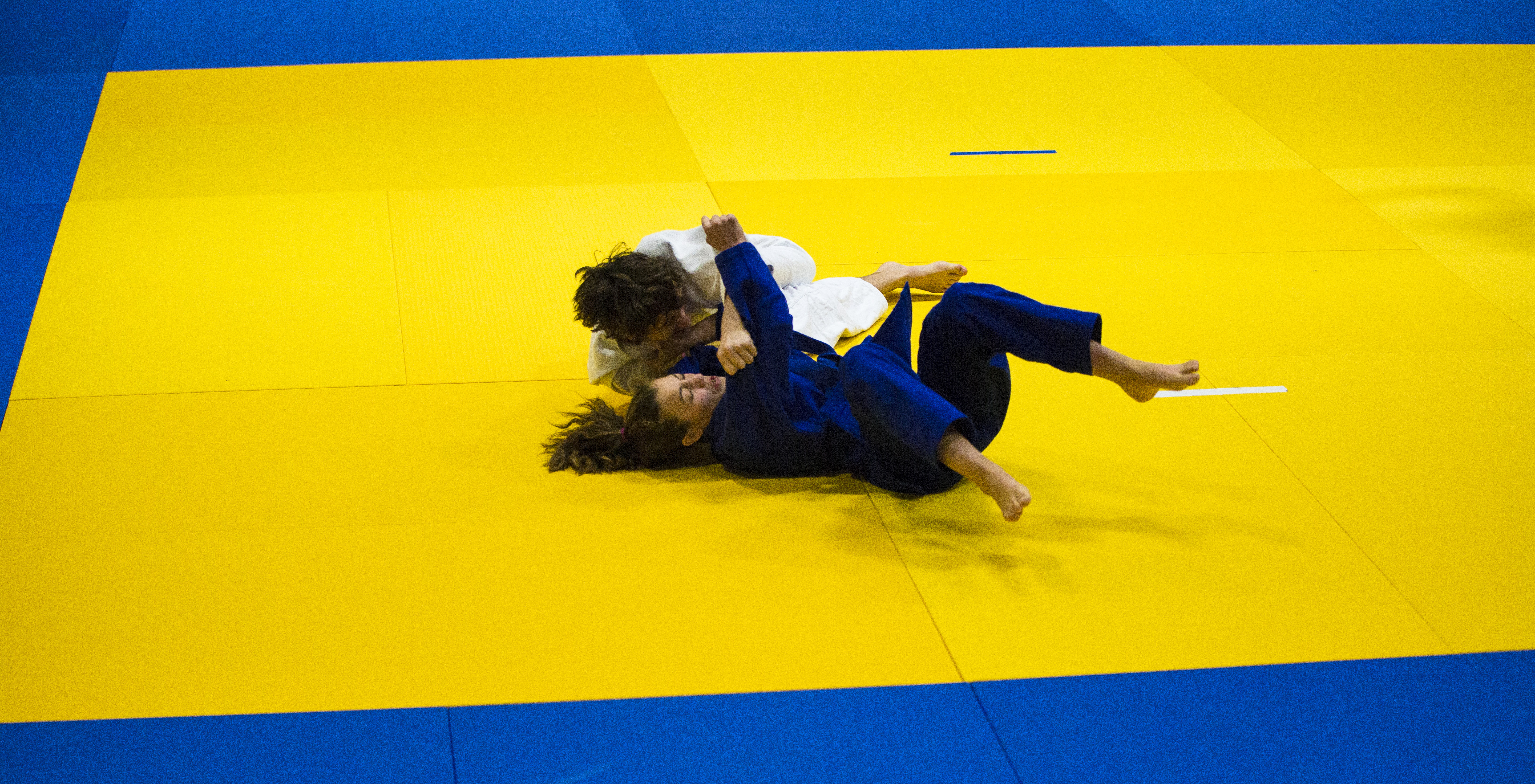 Cassi Jensen and her opponent tangle limbs during a match. Competitors take part in a judo tournament at Golden Horn Elementary School on Oct. 22, 2016. It was the first tournament of the season. Photo by Marissa Tiel