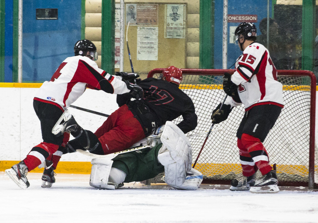 Kaleb Dawe of the Whitehorse Huskies shoves North Island Capital Jack Kennelly into Huskies starting goalie Jon Olthuis as Burt Stephens (15) looks on during second period round-robin Coy Cup action at the Takhini Arena on March 28, 2017. Olthuis left the game shortly after and did not return. The Huskies won 6-3.