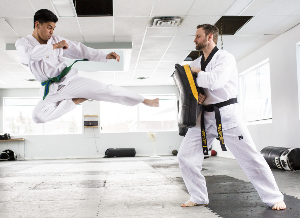 John Kempis and Nathan Cross, members of the Fighting Tiger Taekwondo club in Whitehorse pose for photographs at Peak Fitness after returning from their first competition with gold and silver medals. Photo by Marissa Tiel