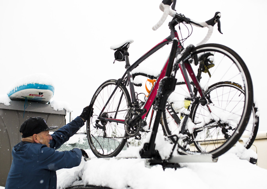 Dan Reimer loads a road bike onto his car south of Haines Junction after snow cancelled the Kluane Chilkat International Bike Relay early Saturday June 17, 2017.