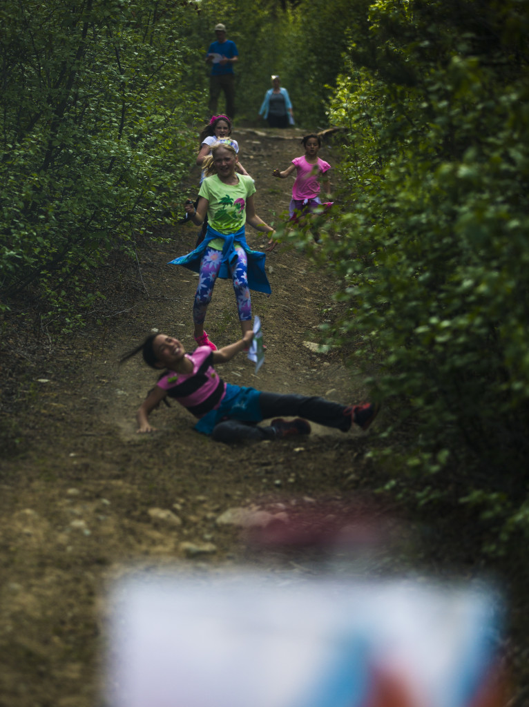 Aurelia Koh takes a tumble as Annie McNeill (green), Avery Kinsella and Iliana Koh follow down the hill to the final control before the finish during the Yukon Orienteering Middle Distance Championships in the Lo-Bird subdivision on Wednesday, June 7, 2017.